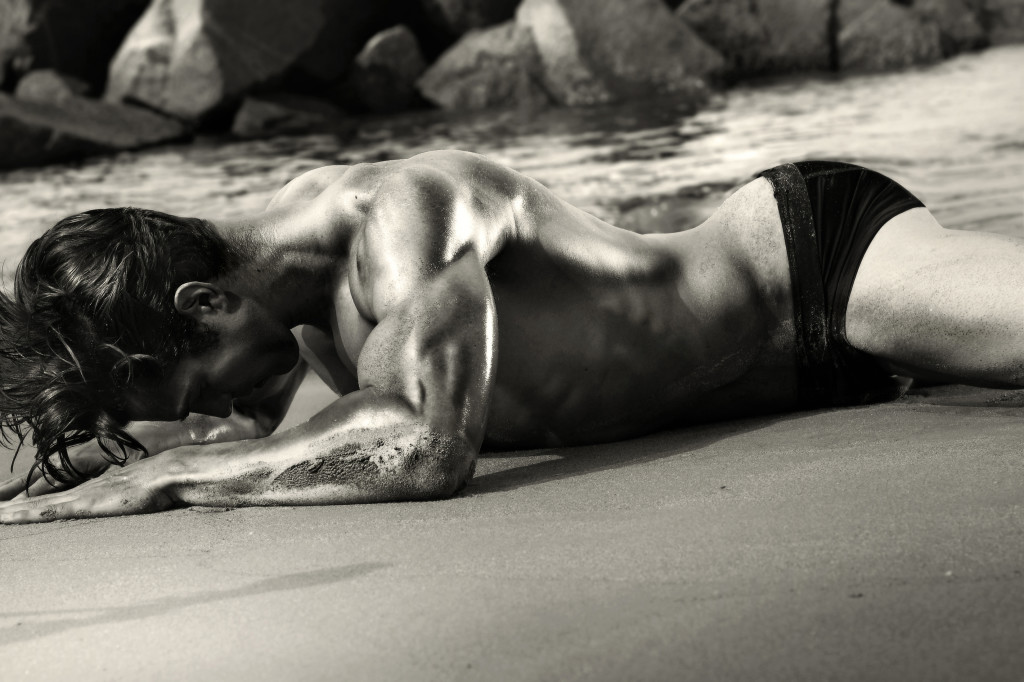 Sexy black and white image of man crawling on beach in only his black briefs.