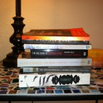 The books Jade is currently reading, stacked on her nightstand.