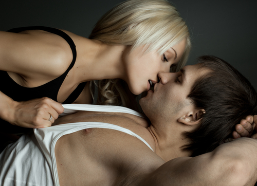 Woman lying on top of man tugging at his shirt seductively
