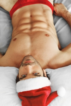 Sexy topless man in a Santa hat