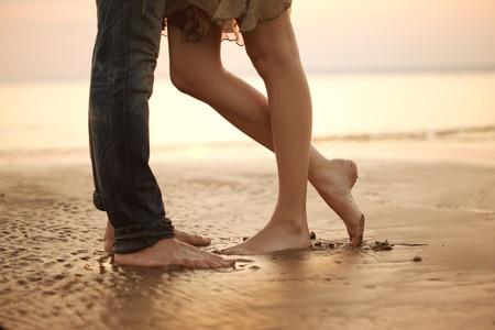 Legs of couple kissing on beach