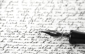 B/W image of calligraphic pen resting on handwritten note