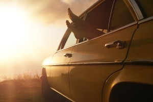 Picture of feet sticking out of car window, parked to watch sunset