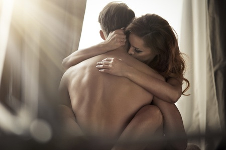 Couple holding each other as morning light streams in window