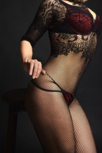 Image of woman playing with panties over fishnets
