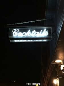 Photo of a neon cocktails sign against black sky